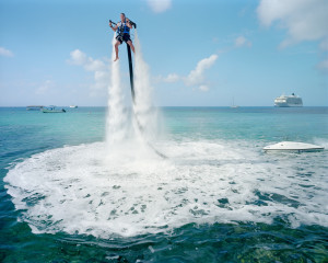 "© Paolo Woods-Gabriele Galimberti _The Heavens. An employee of ""Jetpack Cayman"" demonstrates this new watersport, now available on the island. A 2000cc motor pumps water up through the Jetpack, propelling the client out of the sea (359 USD for a 30-minute session). Mike Thalasinos, the owner of the company, remarks, ""The Jetpack is zero gravity, the Cayman are zero taxes, we are in the right place!"" Grand Cayman."